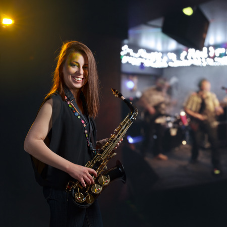 happy  woman with a saxophone  in nightclub photo