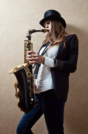 glam rock: young beautiful woman in black hat with saxophone Stock Photo