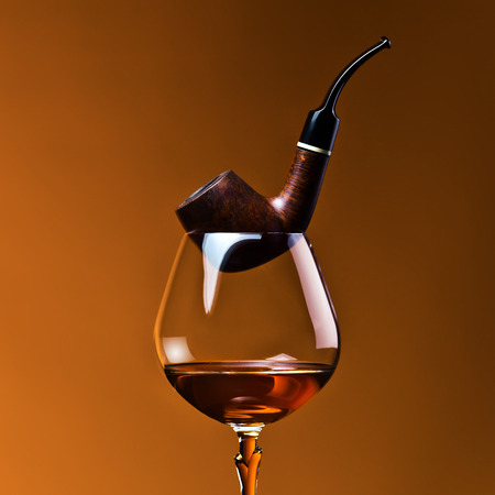 snifter: pipe and snifter with brandy on  dark  Stock Photo