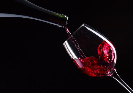 bouteille de vin: bouteille et un verre de vin rouge sur fond noir