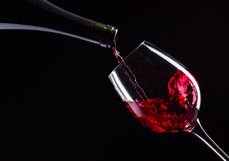 fles en glas met rode wijn op zwarte Stockfoto