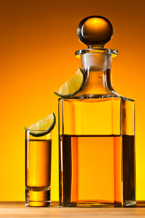 gold tequila  and lime on wooden table photo