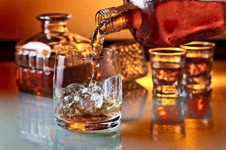 botella de licor: vaso con whisky y hielo en una mesa de cristal