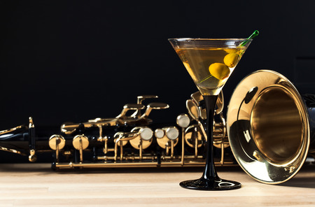 jazz: saxophone and martini with green olives on wooden table