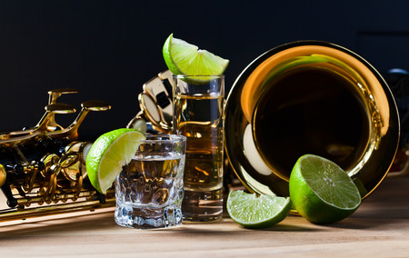 saxophone and tequila with lime on wooden table Imagens
