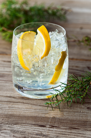 alcoholic drink with lemon and ice on a old wooden table photo