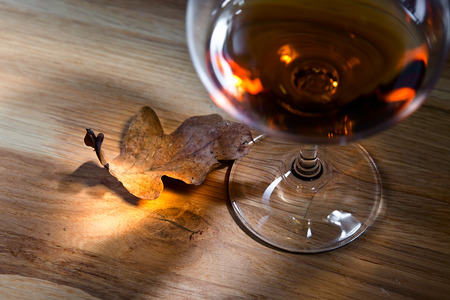 snifter: snifter with brandy on a old oak table