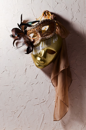 Two golden Venetian masks on  old wall photo