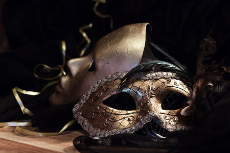 Old gold Venetian masks on a wooden table photo