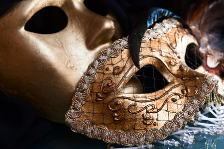 Old gold Venetian masks on a glass table photo