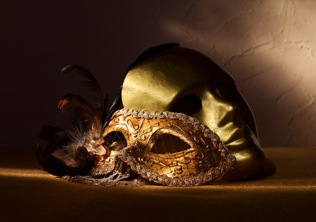 masquerade mask:  Two golden Venetian masks , focus on foreground