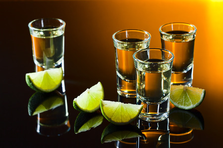 tequila and lime on a black glass table photo