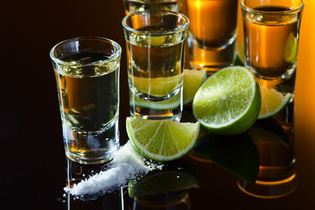 tequila , salt and lime on a black glass table. photo