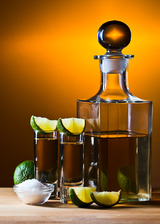 gold tequila with salt and lime on wooden table photo