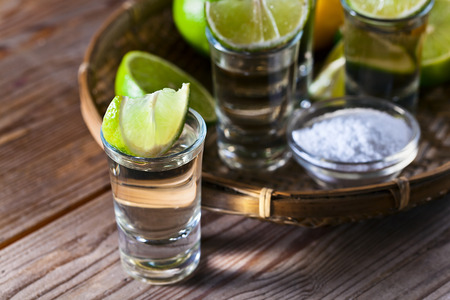 gold tequila with salt and lime on old wooden table. photo