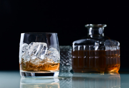 glass with whiskey and ice on a glass table  photo