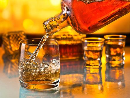 botella de whisky: vaso con whisky y hielo en una mesa de cristal