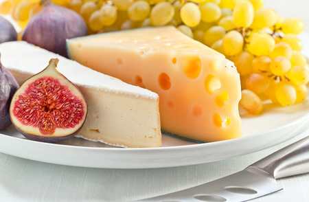 cheese with fruits on a white plate photo