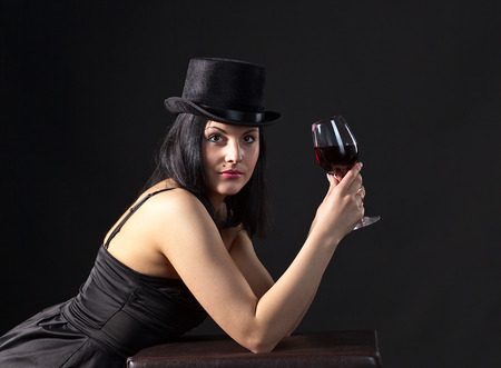 young beautiful woman in black  with red wine photo