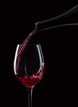 bottle and glass with red wine on  black background photo