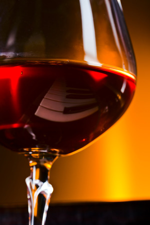 snifter: snifter with brandy on a old piano