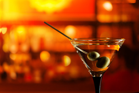 horizontal bar: glass with martini , focus on a olives Stock Photo