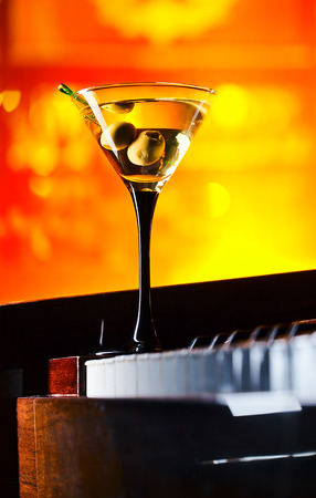 glass with martini on a old piano in bar photo