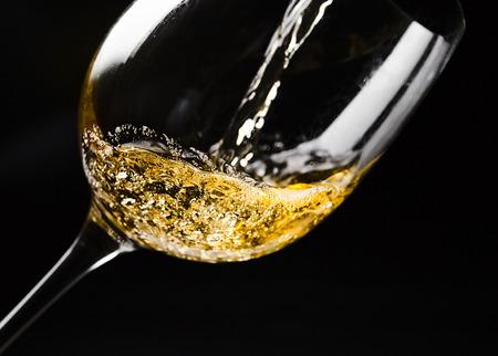 vidrio: Vino blanco que se vierte en una copa de vino en el fondo negro