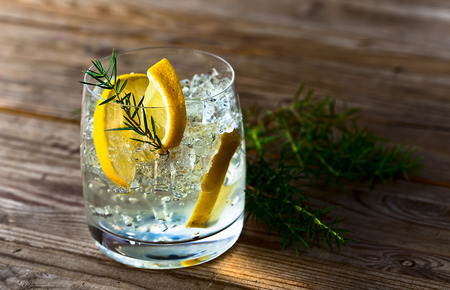 gin: alcoholic drink with lemon and ice on a old wooden table Stock Photo