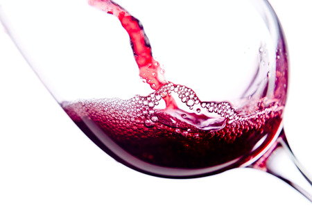 red wine pouring: Red wine in wineglass on white background