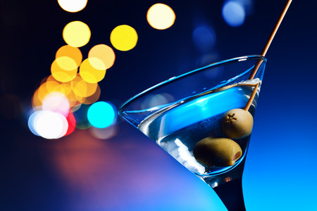 horizontal bar: dry martini with olives ,focus on a berry