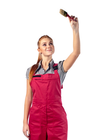 Young woman in red overalls with brush , isolated on white photo
