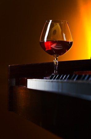 snifter with brandy on a old piano