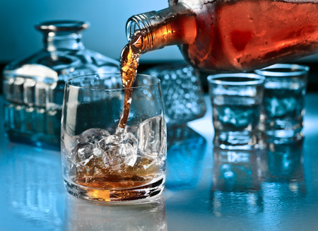 alcoholic drink: glass with whiskey and ice on a glass table