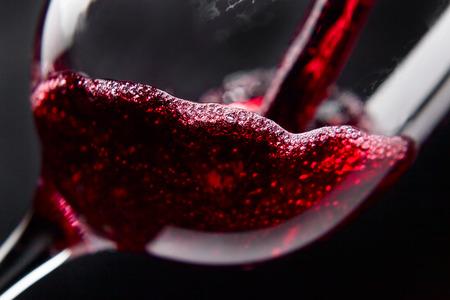 Rode wijn in wijnglas op zwarte achtergrond