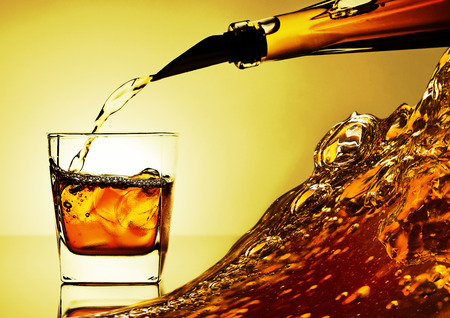 alcoholic drink: alcoholic drink  being poured into a glass with ice Stock Photo