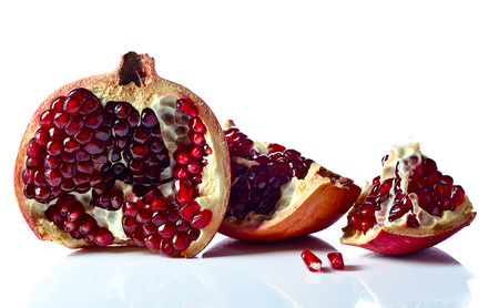 reflexive: ripe pomegranate isolated on a white reflexive background