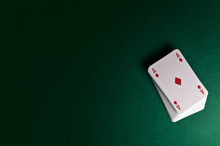 background card: playing cards on green table in cacino