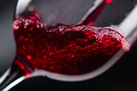 copa de vino: El vino tinto en copa de vino en el fondo negro Foto de archivo