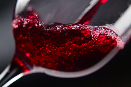 Red wine in wineglass on  black background Archivio Fotografico