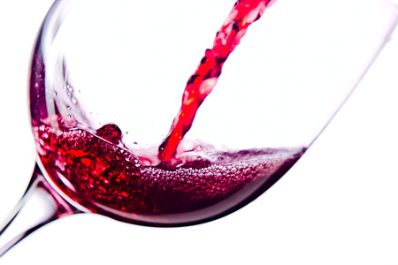 pouring wine: Red wine in wineglass on white background