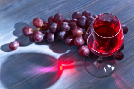 copa de vino: vino tinto y las uvas de mesa de madera azul Foto de archivo