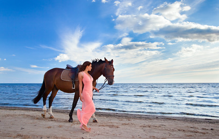 womanl in pink dress with horse on seacoast photo