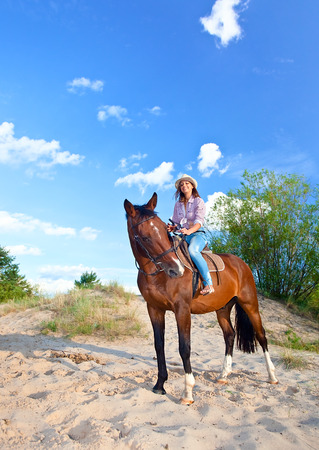 young beautiful woman with horse in forest photo