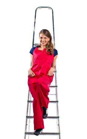 jumpsuit: young woman in a red jumpsuit on  ladder, isolated on white Stock Photo