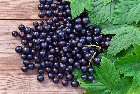 zwarte bessen en groene bladeren op houten tafel Stockfoto