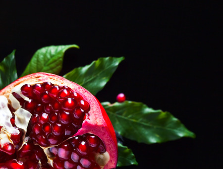 eating fruit: pomegranate with leaves on a black background