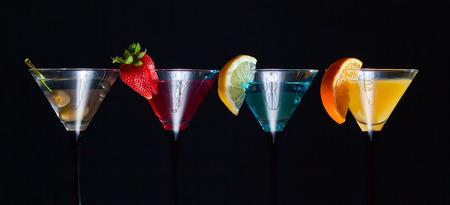 longdrink: Different cocktails garnished with fruits on black background