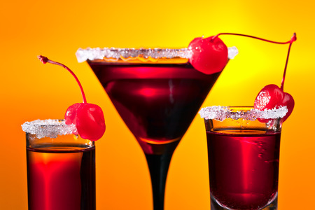 alcoholic drinks: alcoholic drinks with sweet cherry on yellow background Stock Photo