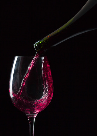 pouring wine: bottle and glass with red wine on  black background
